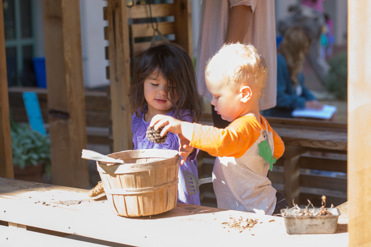Older Toddlers play in the outdoor classroom kitchen hut